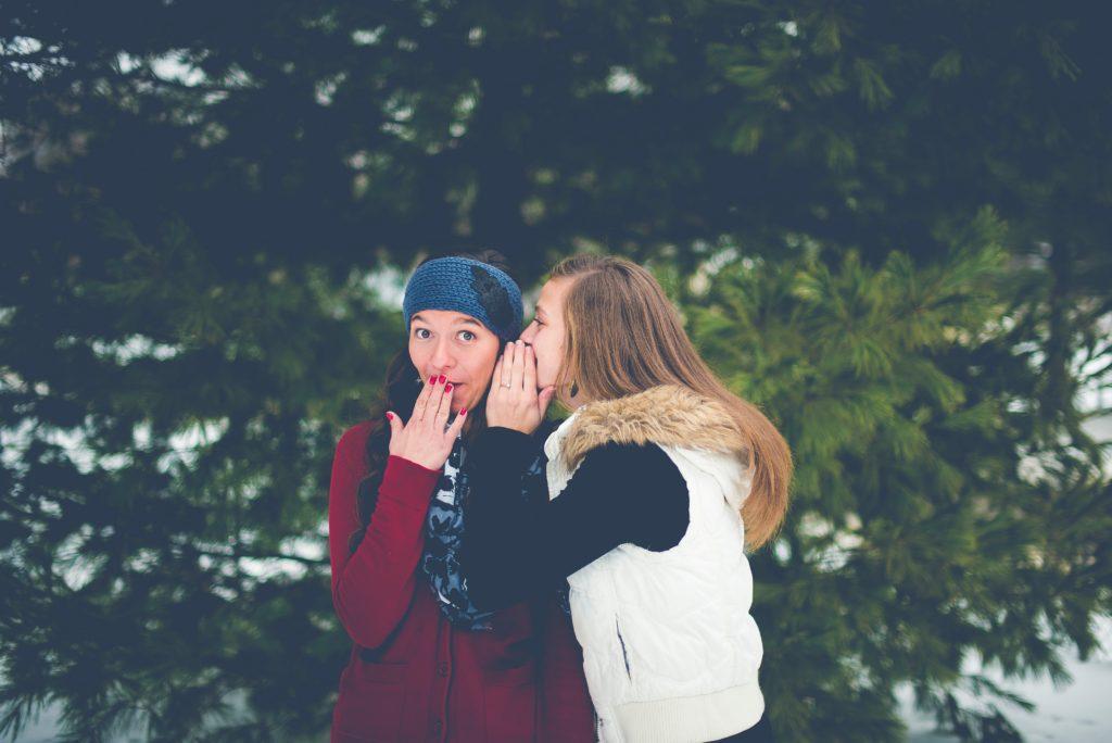 Vrouwen die een geheim vertellen.