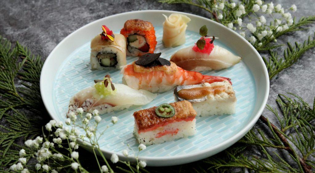 Ideer til firmaevent kan omfatte lækker udenlandsk mad som denne plade af sushi og sashimi