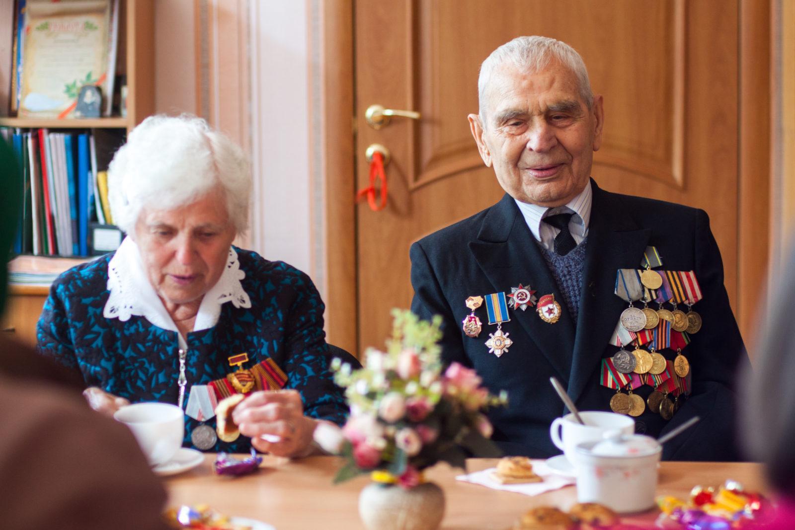 Een oudere man en een vrouw zitten aan een tafel