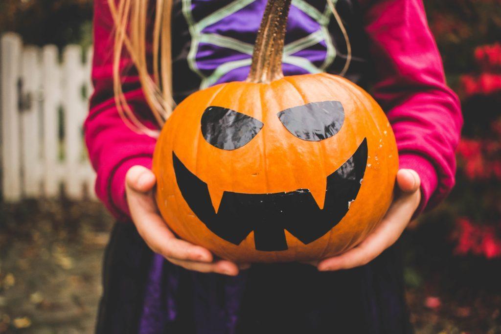 Halloween Event Ideen: Kürbisschnitzen ist ein Klassiker. Dieses Kind hat das Memo über das Schnitzen nicht bekommen.